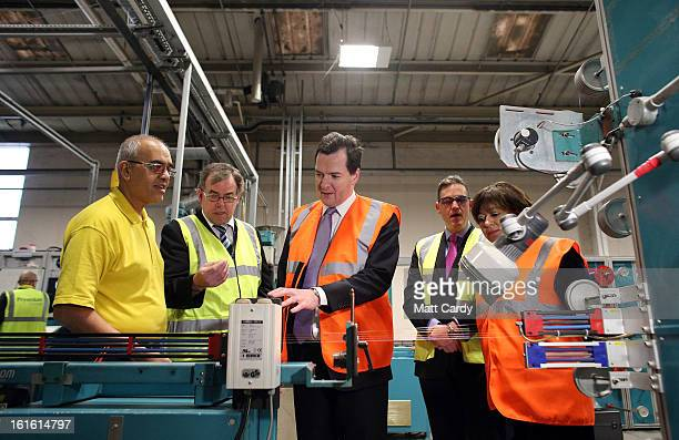 Chancellor George Osborne wears a high visibility jacket as he makes a visit to the Prysmian Group factory and speaks to employee Raj Guru factory...