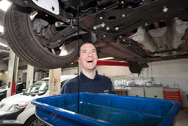 Chancellor George Osbourne watches as old oil is drained from a car that is being serviced in the service and repair workshops as he meets...