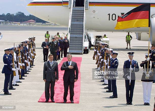 Chancellor Gerhard Schroeder of Germany and Deputy US Chief of Protocol Jeff Eubank stand on the red carpet during their national anthems at his...
