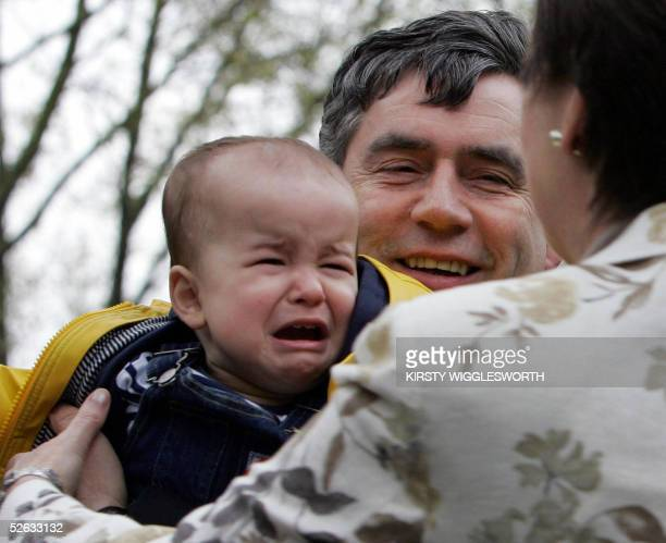 Chancellor Gordon Brown hands back Felix Williams after he started to cry during a visit to Comber Grove primary school in Camberwell south London 15...