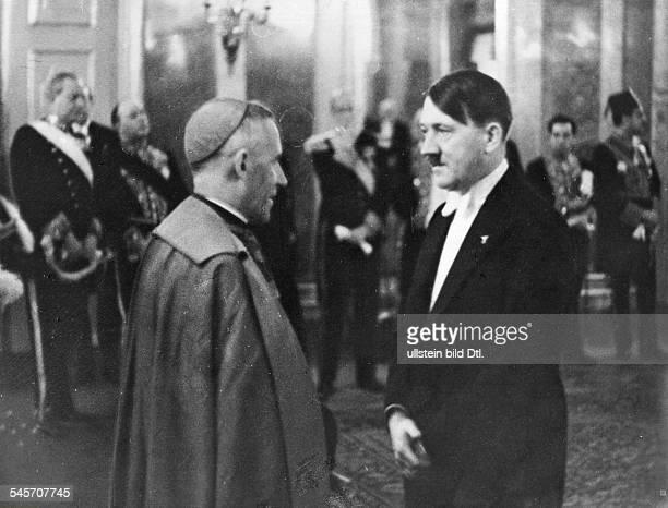 ADOLF HITLER Chancellor of Germany 193345 Hitler in conversation with papal Nuncio Cesare Orsenigo at a New Year's recption for foreign diplomats...