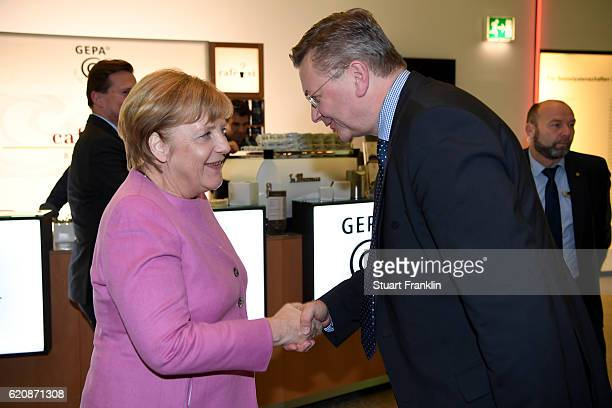 Chancellor of Germany Angela Merkel shakes hand with DFB President Reinhard Grindel during the ceremonial act of the 42nd DFB Bundestag at Theater...