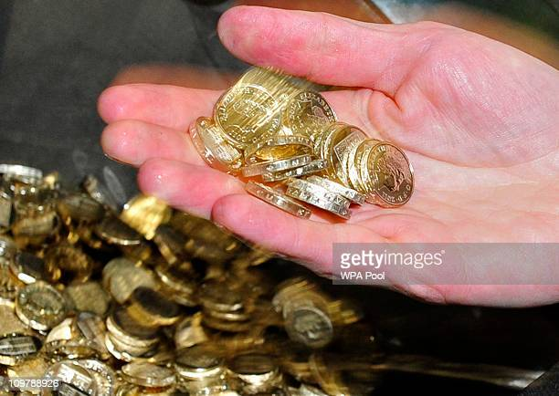 Chancellor of the Exchequer George Osborne handles newly minted one pound coins during a visit to the Royal Mint in Cardiff March 5 2011 Britain's...