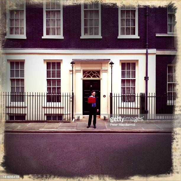 Chancellor of the Exchequer George Osborne poses for photographers outside 11 Downing Street before presenting his annual budget to Parliament on...