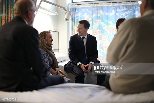 Chancellor of the Exchequer George Osborne sits on a bed as he talks with staff and patients during a visit to the Research Innovation Learning and...