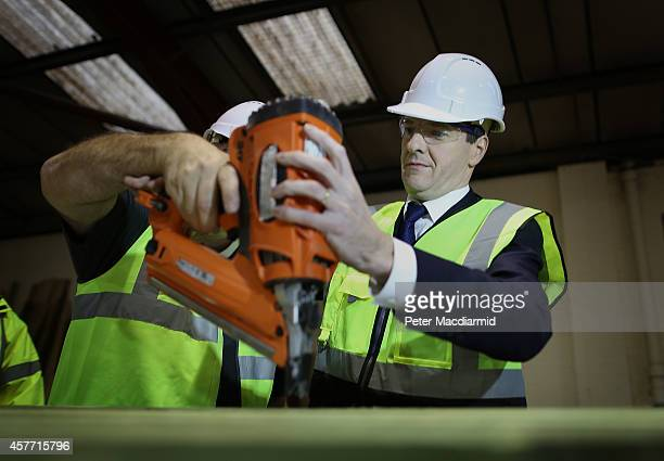 Chancellor of the Exchequer George Osborne uses a nail gun during a visit to Rotunda Living a manufacturer of wooden buildings on October 23 2014 in...