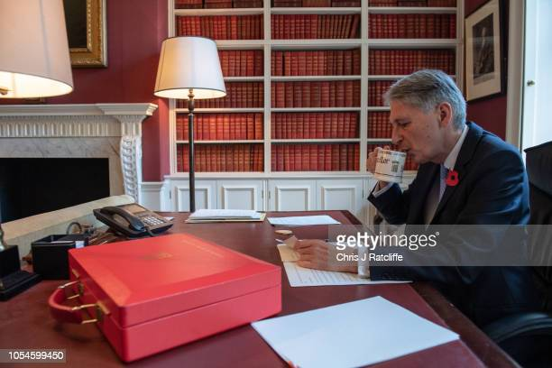 Chancellor of the Exchequer Philip Hammond drinks tea as he prepares his speech in his office in Downing Street ahead of his 2018 budget announcement...