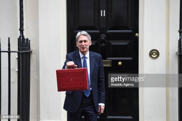 Chancellor of the Exchequer Philip Hammond holds the budget box up to the media as he leaves 11 Downing Street in London United Kingdom on March 08...