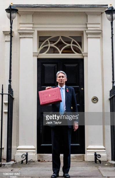 Chancellor of the Exchequer Philip Hammond holds the red case as he departs 11 Downing Street to deliver his 2018 budget announcement to Parliament...