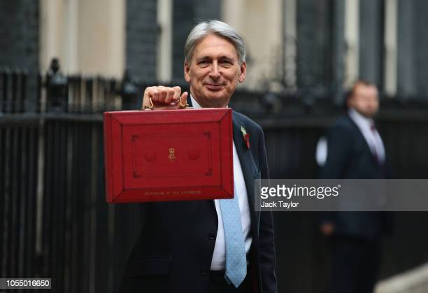 Chancellor of the Exchequer Philip Hammond presents the red Budget Box as he departs 11 Downing Street to deliver his 2018 budget announcement to...