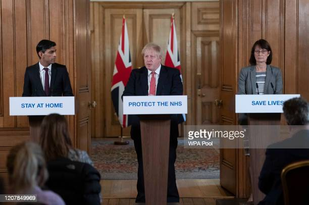 Chancellor of the Exchequer Rishi Sunak and Deputy Chief Medical Officer Dr Jenny Harries look on as British Prime Minister Boris Johnson speaks...