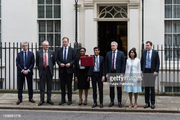 Chancellor of the Exchequer Rishi Sunak holds the budget box as he stands together with his treasury team including Chief Secretary to the Treasury...