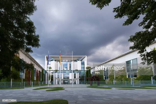 Chancellor's office with dark clouds, framed by trees, Berlin, Germany