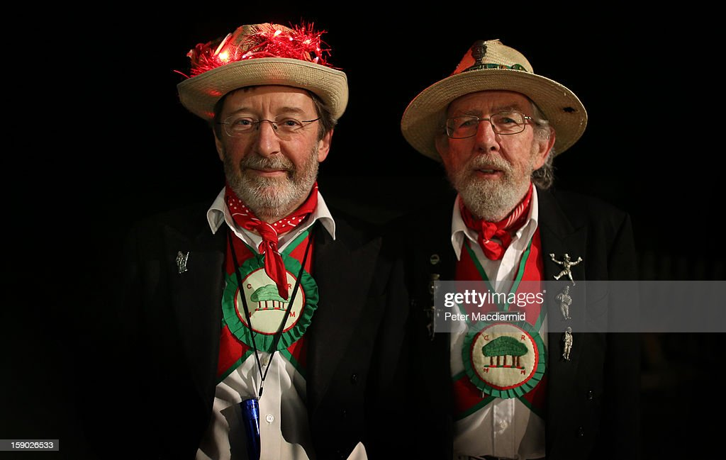 Chanctonbury Ring Morris Men Richard Lelliott (L) and Master of Ceremonies Doug Parrot wait for a drink of cider after the Apple Howling ceremony at Old Mill Farm on January 5, 2013 in Bolney, England. In this ancient ritual villagers surround the oldest and largest tree in the orchard and evil spirits are driven out and good spirits are encouraged to produce a bountiful apple crop for the following year's cider drink.