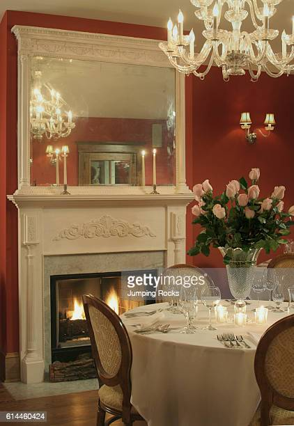 Chandelier above table set for dinner in red dining room with lit fire
