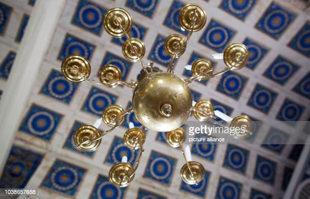 A chandelier hangs from the coffered ceiling designed as a starry sky can be seen in the vault of the village church of Benz Germany 18 June 2016 The...