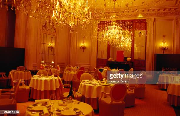 Chandeliers and set tables inside Alain Decasse au Plaza Athenee.