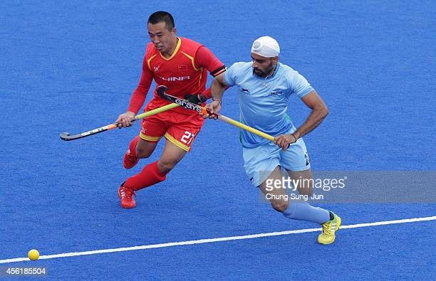 Chandi Gurwinder Singh of India competes for the ball with Sun Tianjun of China during the Hockey Men's Pool B match between India and China during...