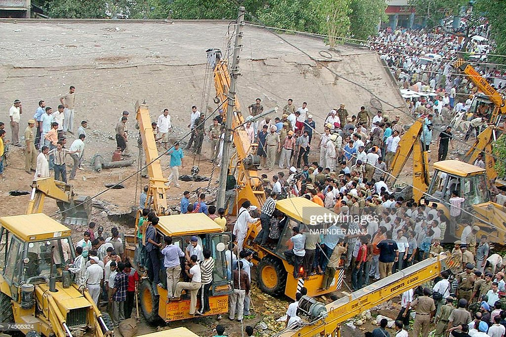 Indian rescue workers remove debris after the roof collapsed at vegetable market in Chandigarh 10 June 2007 Two people were killed and several...