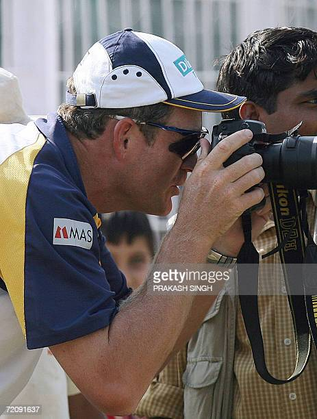 Sri Lankan cricket team's coach Tom Moody watches a practice match against the Punjab Team through a camera in Chandigarh 05 October 2006 Sri Lanka...