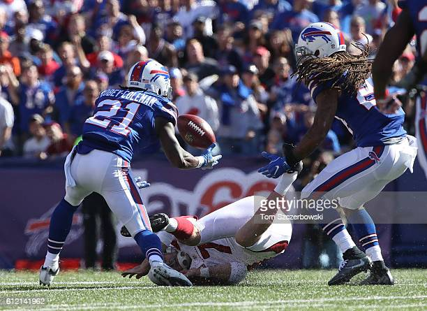 Chandler Catanzaro of the Arizona Cardinals tries to recover a bad snap during NFL game action as Nickell RobeyColeman of the Buffalo Bills goes...