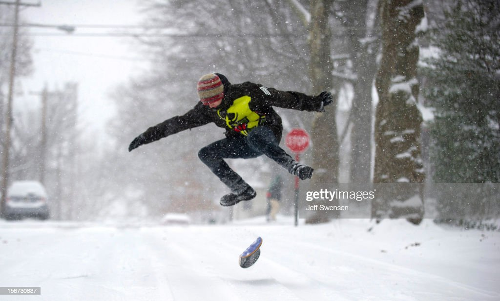 Chandler Fescemeyer, 17, snowboards down the road after a winter storm blanketed the Midwest with snow December 26, 2012 in Pittsburgh, Pennsylvania. The storm has moved west from the Sierra Nevada across the Midwest and will head to the East Coast today.