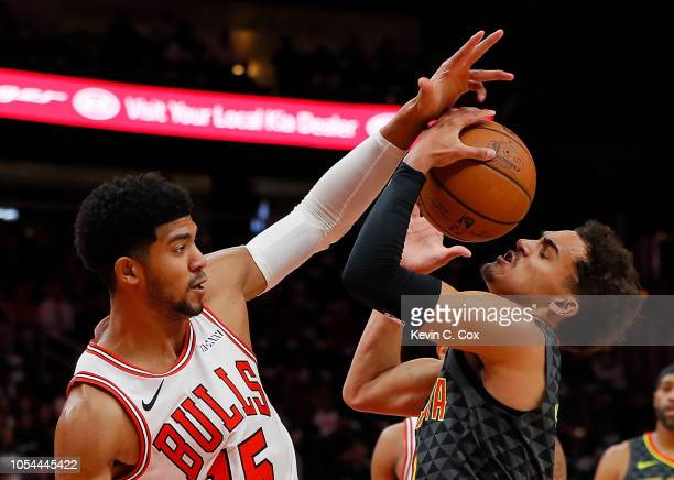 Chandler Hutchison of the Chicago Bulls defends against Trae Young of the Atlanta Hawks at State Farm Arena on October 27 2018 in Atlanta Georgia...