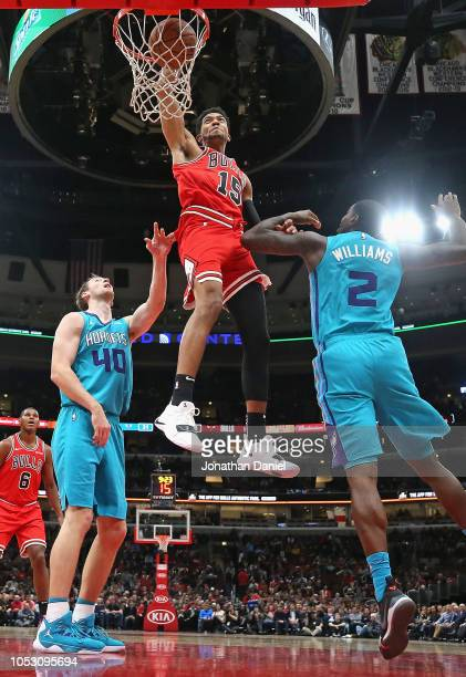 Chandler Hutchison of the Chicago Bulls dunks over Cody Zeller and Marvin Williams of the Charlotte Hornets at the United Center on October 24 2018...