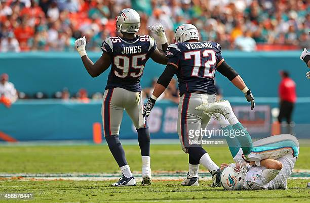 Chandler Jones and Joe Vellano of the New England Patriots celebrate a sack on Ryan Tannehill of the Miami Dolphins during a game at Sun Life Stadium...