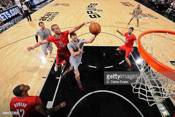 Chandler Parsons of the Houston Rockets blocks a shot against Manu Ginobili of the San Antonio Spurs during the game at the ATT Center on December 25...