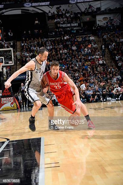 Chandler Parsons of the Houston Rockets drives against Manu Ginobili of the San Antonio Spurs at the ATT Center on November 30 2013 in San Antonio...