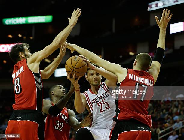 Chandler Parsons of the Houston Rockets drives between Jose Calderon Ed Davis and Jonas Valanciunas of the Toronto Raptors at the Toyota Center on...