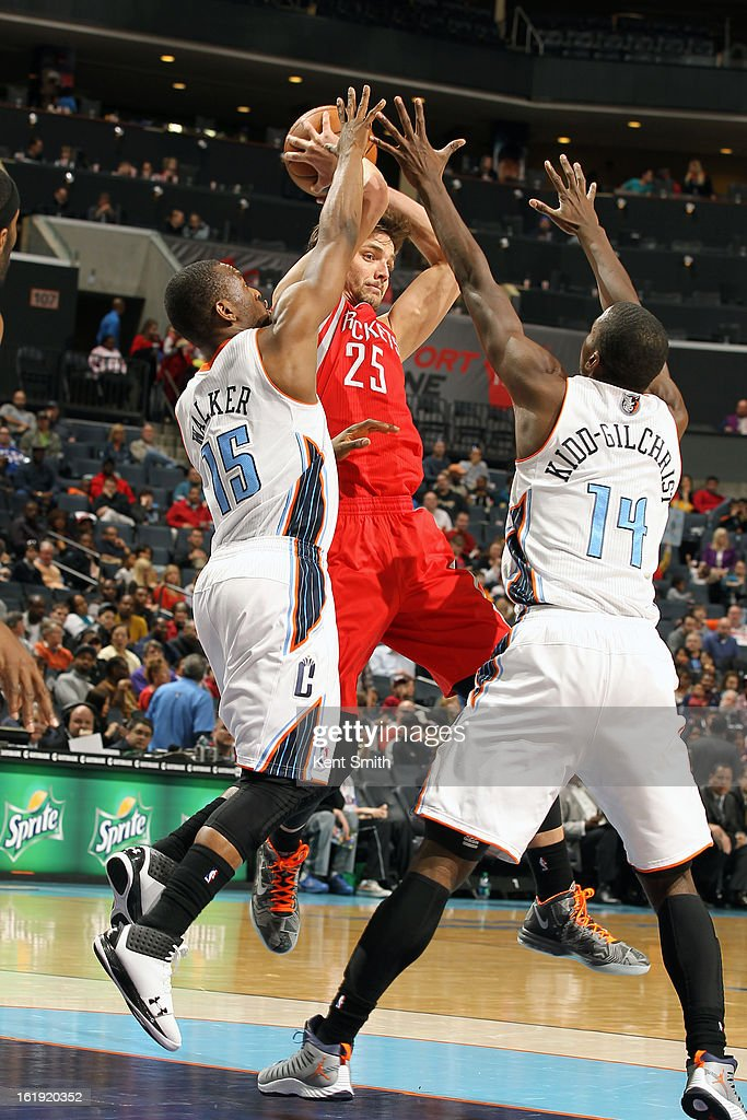 Chandler Parsons #25 of the Houston Rockets passes the ball against Kemba Walker #15 and Michael Kidd-Gilchrist #14 of the Charlotte Bobcats at the Time Warner Cable Arena on January 21, 2013 in Charlotte, North Carolina.