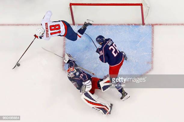 Chandler Stephenson of the Washington Capitals attempts to shoo the puck on Sergei Bobrovsky of the Columbus Blue Jackets as Thomas Vanek of the...