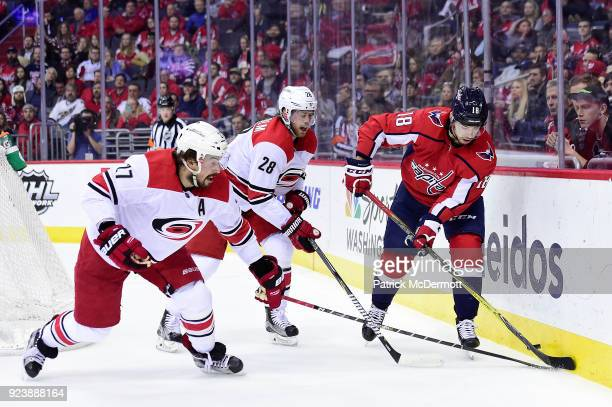 Chandler Stephenson of the Washington Capitals battles for the puck against Justin Faulk and Elias Lindholm of the Carolina Hurricanes in the first...