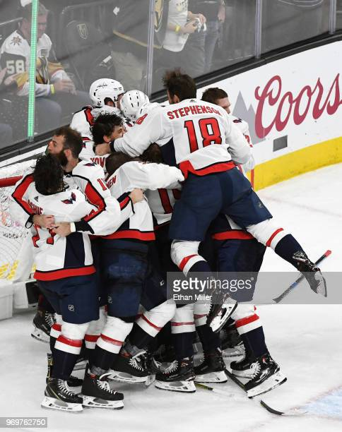 Chandler Stephenson of the Washington Capitals leaps into his teammates as they celebrate their 43 win over the Vegas Golden Knights in Game Five of...
