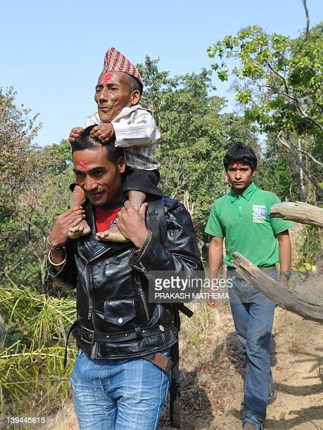 Chandra Bahadur Dangi a 72yearold Nepali who claims to be the world's shortest man at 56 centimetres in height is carried by his nephew Doalk Dangi...