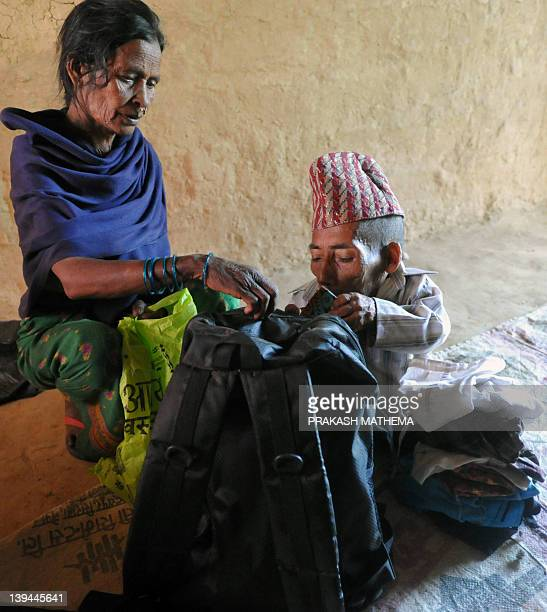 Chandra Bahadur Dangi a 72yearold Nepali who claims to be the world's shortest man at 56 centimetres in height packs his belongings as he prepares to...