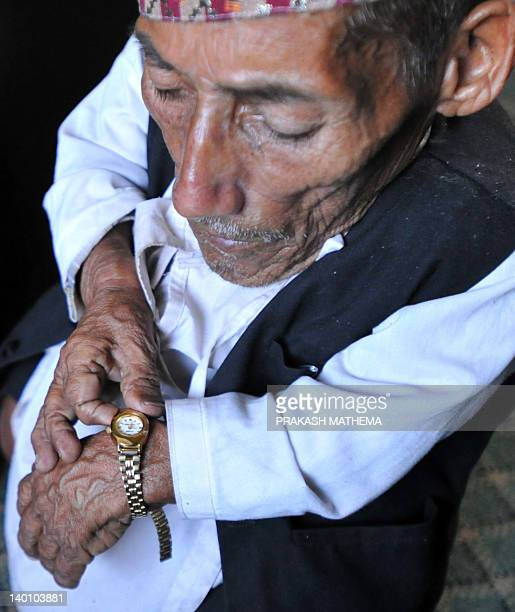 Chandra Bahadur Dangi a 72yearold Nepali who claims to be the world's shortest man at 56 centimetres in height looks at his watch in Kathmandu on...