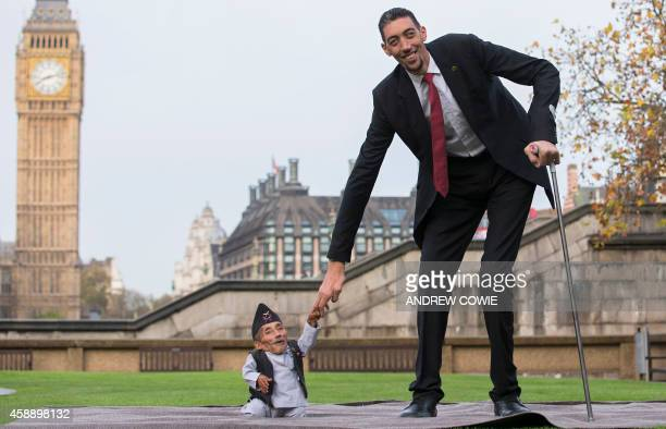 Chandra Bahadur Dangi from Nepal the shortest adult to have ever been verified by Guinness World Records poses for pictures with the world's tallest...