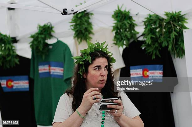 Chandra Carleton looks up from her phone in her booth selling Tshirts and other marijuana related items at Civic Center Park in downtown Denver April...
