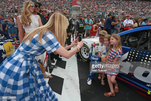 Chandra Johnson takes a picture of Jimmie Johnson driver of the Lowe's Patriotic Chevrolet and his daughters Lydia and Genevieve during prerace...