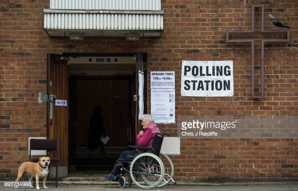 Chanel, a Staffordshire Bull Terrier, is tied up outside a polling station at Tulse Hill Methodist Church as a woman in a wheelchair sits near by on...