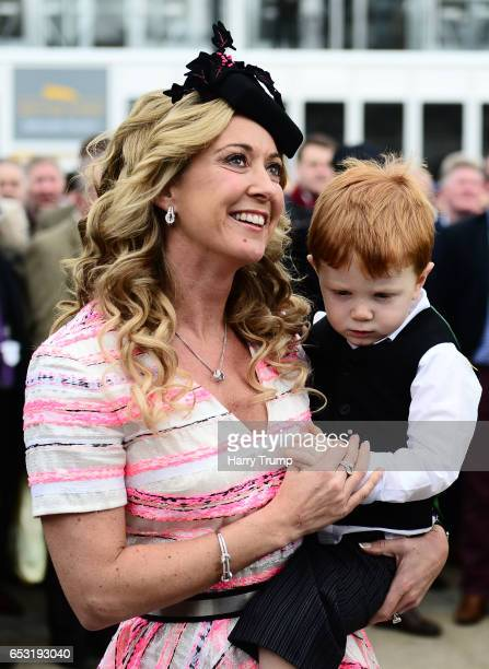 Chanelle McCoy looks on with her son Archie as her husband Sir AP McCoy inveils a statue of himself during Champion Day of the Cheltenham Festival at...