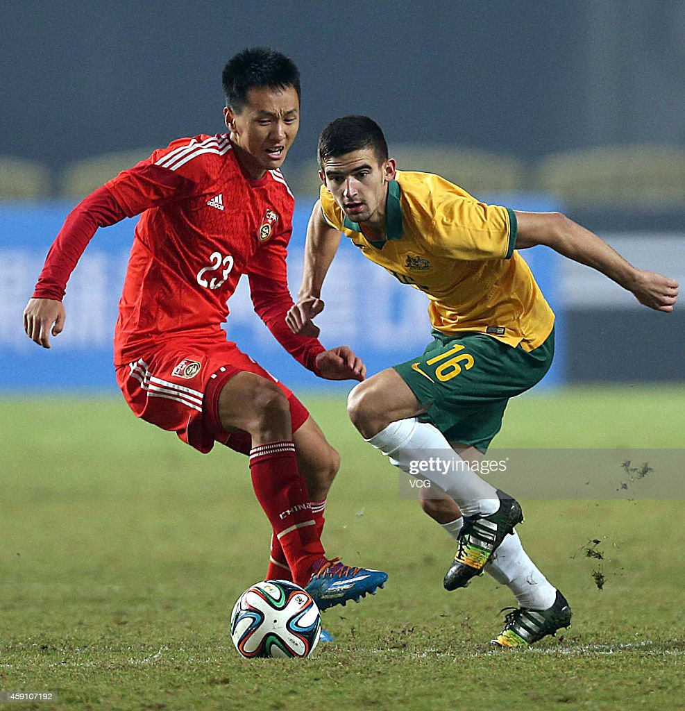 Chang Feiya #23 of China and Steven Peter Ugarkovi #16 of Australia battle for the ball during the match between China U22 and Australia U22 on day three of the 'Wuhan City of Automobile' International Youth Football Tournament at Wuhan Sports Center Stadium on November 16, 2014 in Wuhan, China.