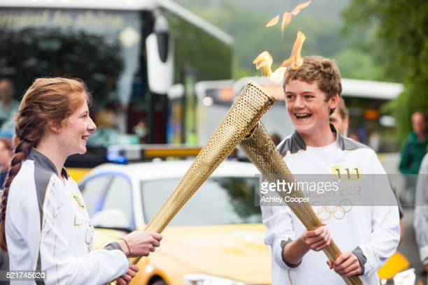 a change over of olympic torch bearers in ambleside, lake district, uk. - the olympic games stock pictures, royalty-free photos & images