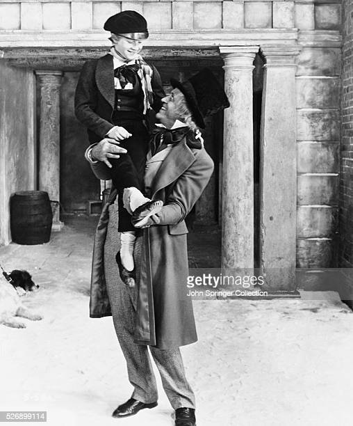 A changed Ebenezer Scrooge holds up Tiny Tim on Christmas morning in A Christmas Carol 1951