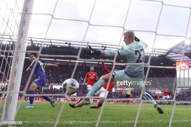 Changhoon Kwon of Freiburg scores his team's first goal past goalkeeper Robin Zentner of Mainz during the Bundesliga match between 1 FSV Mainz 05 and...