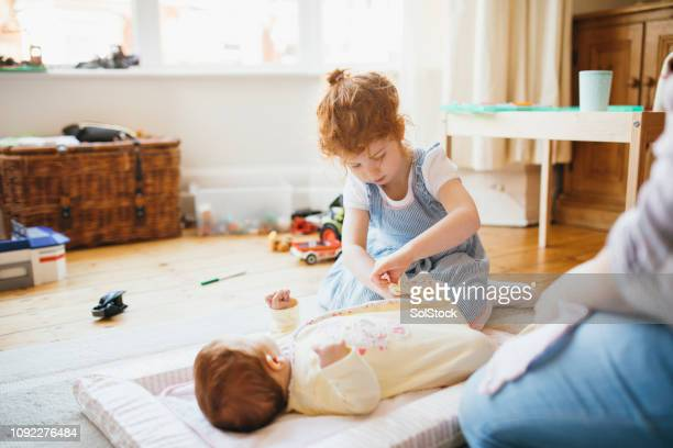 changing her baby sister's diaper - baby changing mat stock pictures, royalty-free photos & images