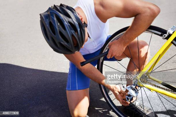 changing his bike tyre - air pump stock photos and pictures